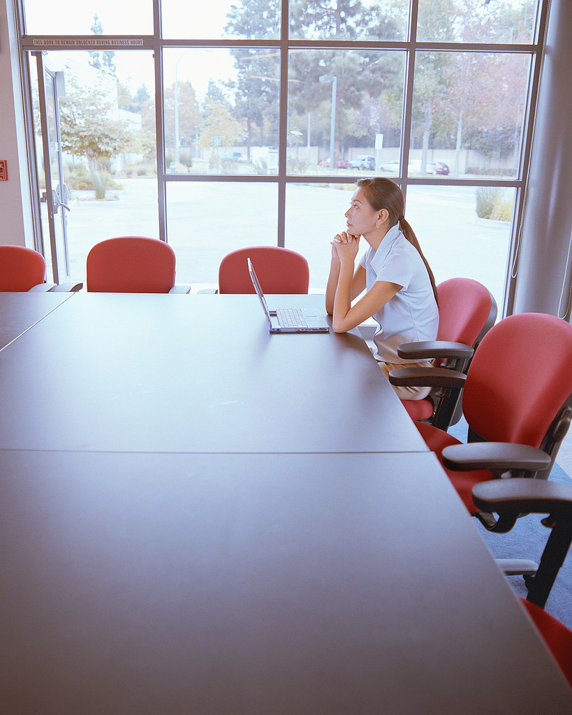 Photo showing woman alone in board room in front of laptop. Edit Your Own Work course photograph